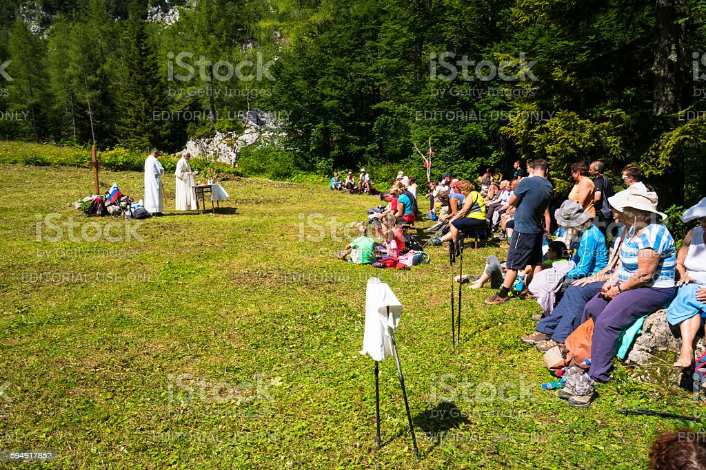 Hikers on open field at Okreselj listening to the Mass stock photo
