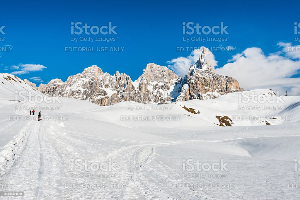 Hikers on path on the snow heading to Dolomites stock photo