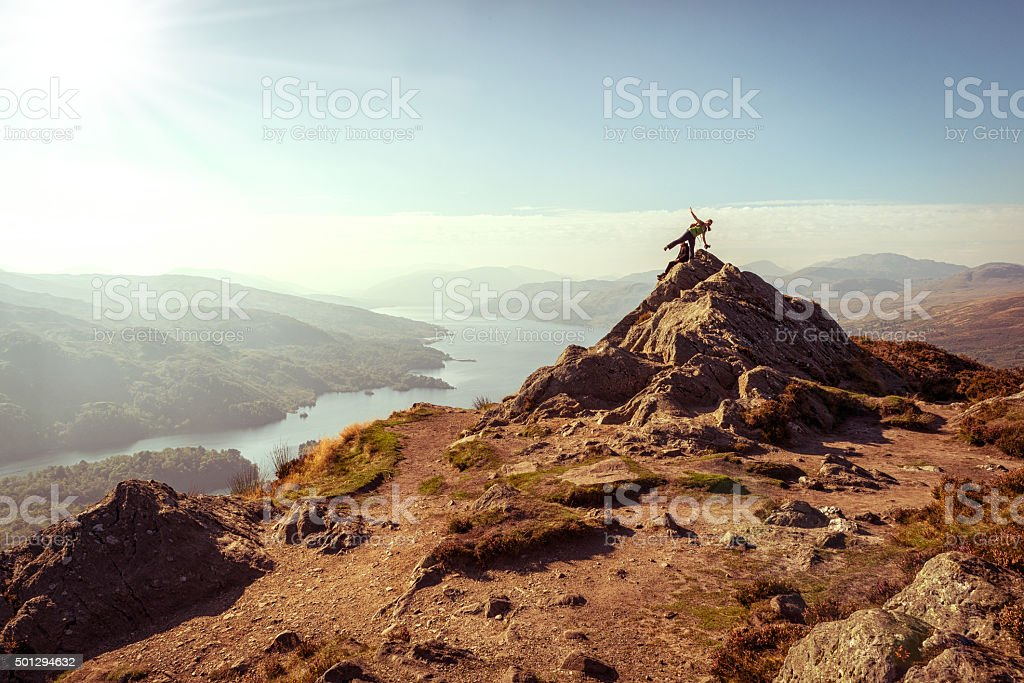 Hikers on top of mountain enjoying view, Loch Katrine, Scotland stock photo