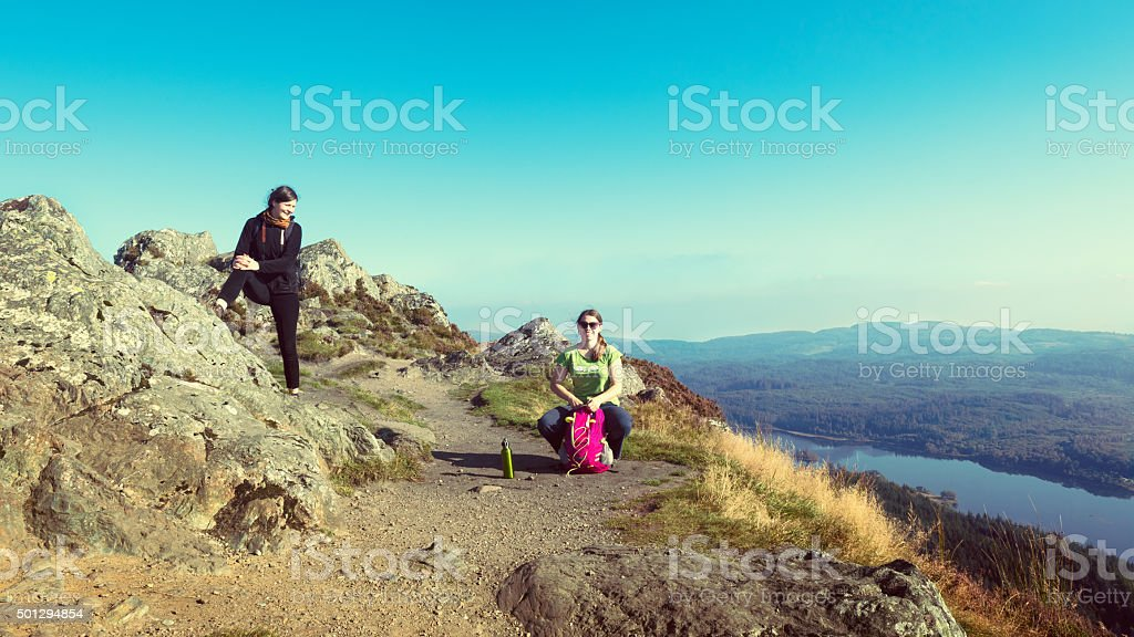 Hikers on top of mountain taking break and enjoying view stock photo