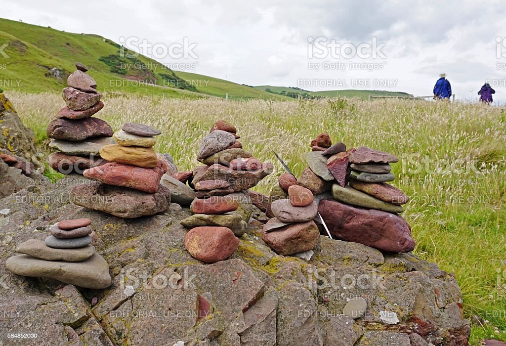 Hikers passing some cairns in a hilly landscape stock photo