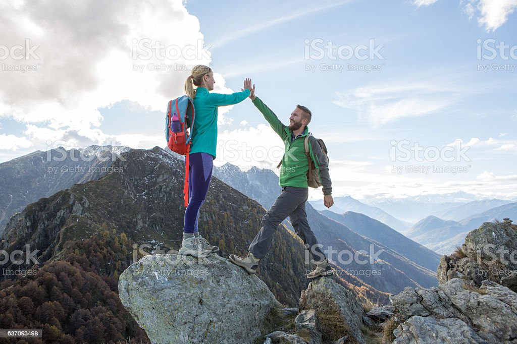 Hikers reaching mountain top celebrating with high five stock photo