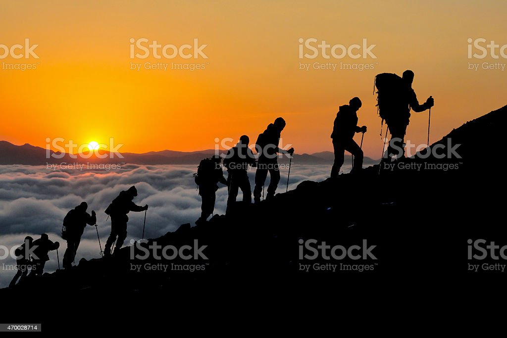 Hikers Silhouetted Against Sunset stock photo