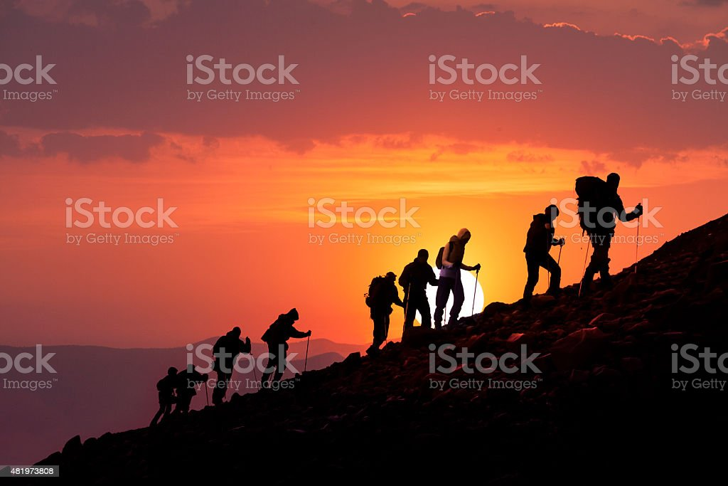 Hikers Silhouetted At Sunset stock photo