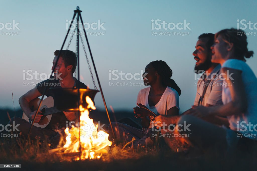 Hikers Singing And Playing Guitar Around Campfire stock photo