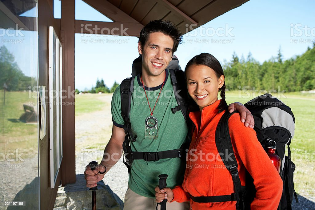Hikers standing by outdoor information wall stock photo