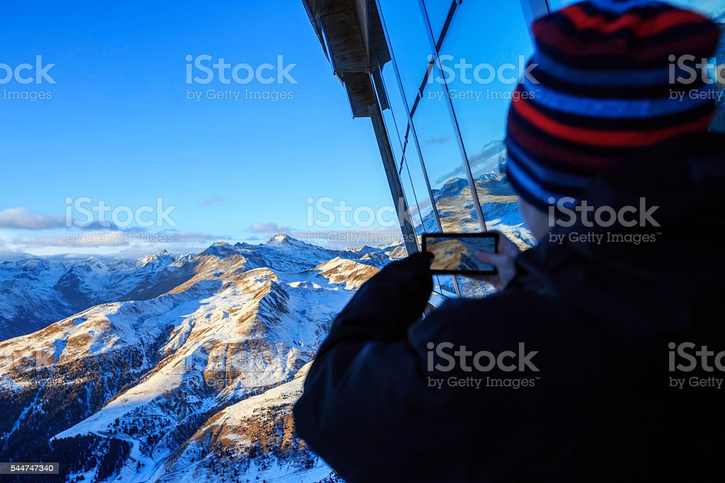 Hikers teens boy photographing winter landscape  Uses touchscreen smartphone stock photo