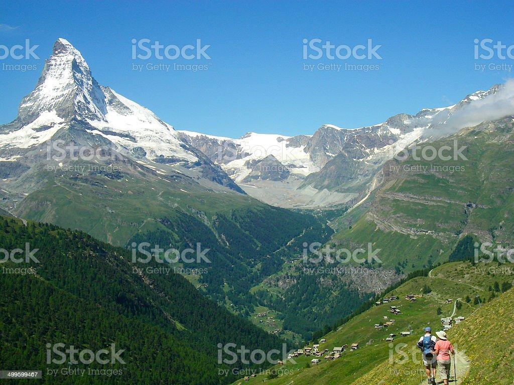 Hikers trail above Zermatt Switzerland with Matterhorn Peak Background stock photo