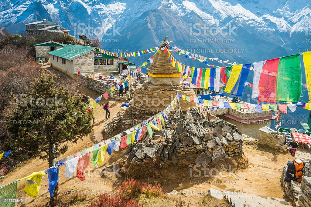 Hikers trekking colourful Buddhist prayer flags Everest trail Himalayas Nepal stock photo