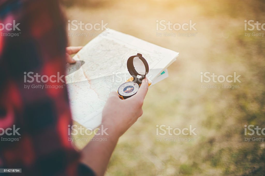 Hikers using compass and map in nature stock photo