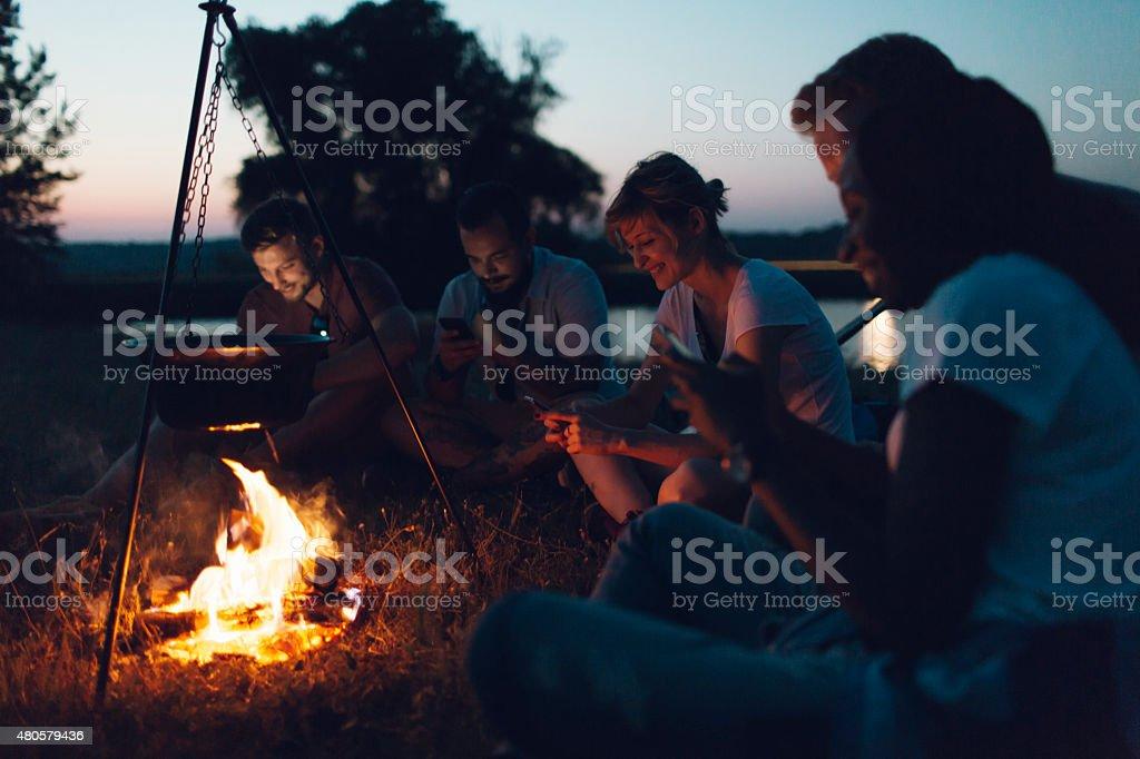 Hikers Using Smart Phones Around Campfire. stock photo