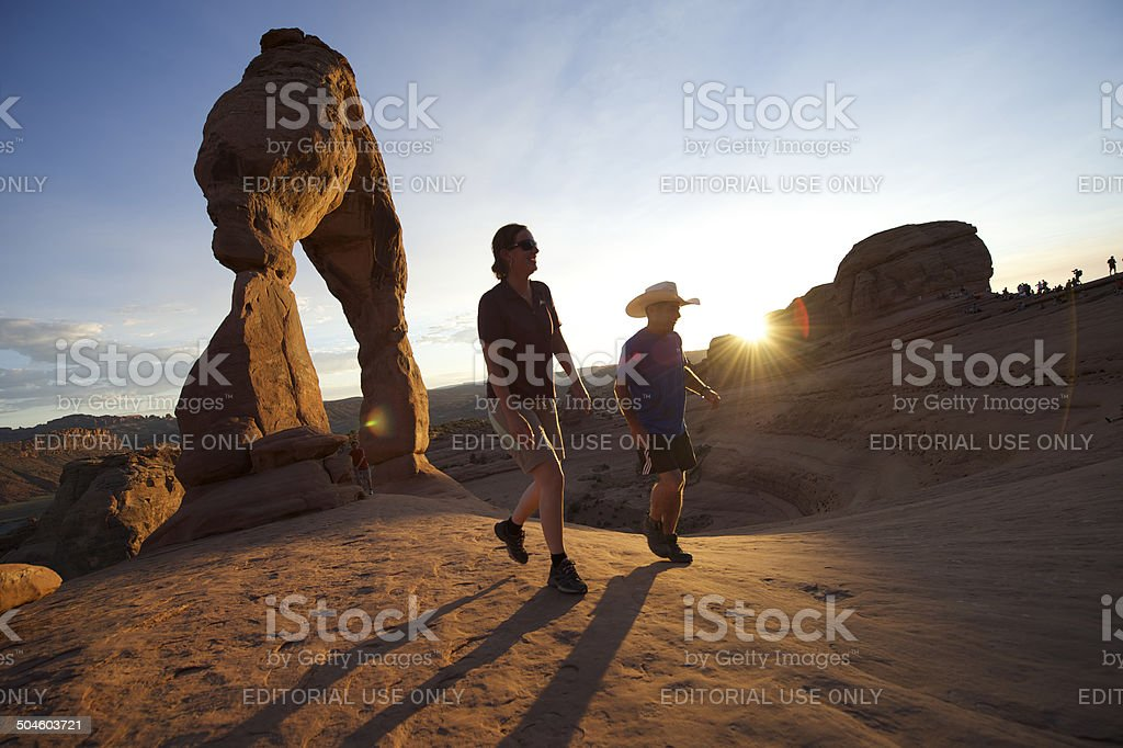 Hikers Walking at Delicate Arch Sunset stock photo