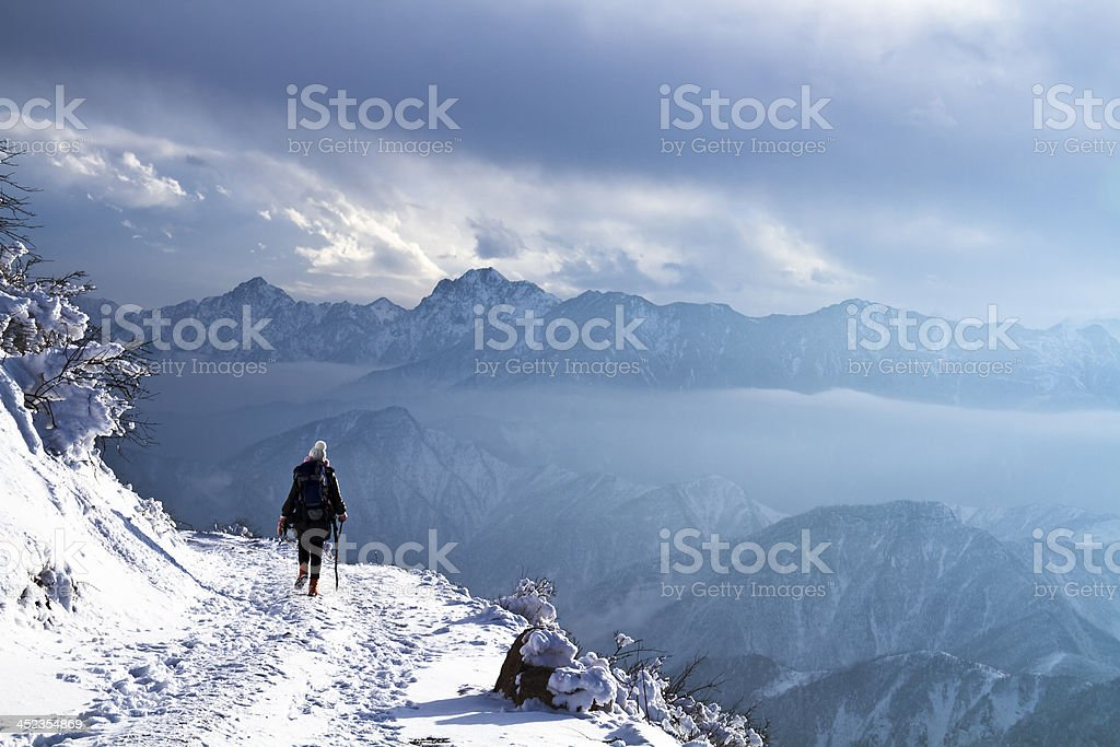 Hikers walking on cliffside path. stock photo