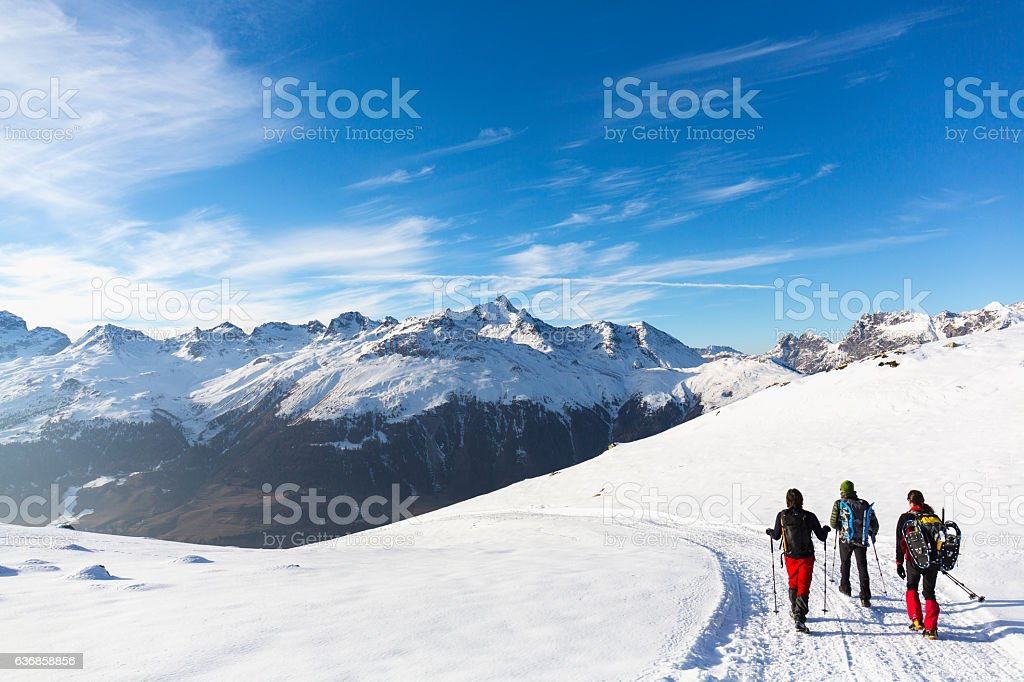 Hikers walking on snow covered road in high mountain stock photo