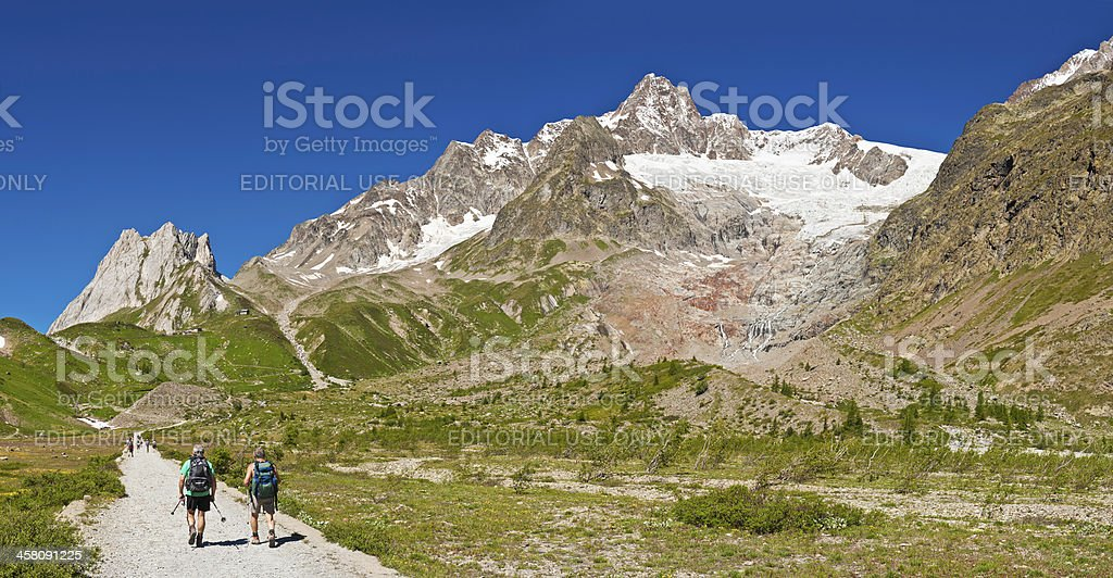 Hikers walking through summer mountain valley Alps Italy royalty-free stock photo