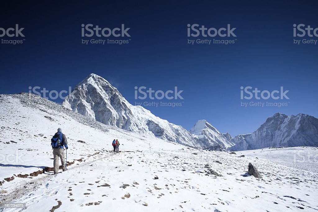 Hikers walking through the snow towards mountain peaks of  Hima stock photo