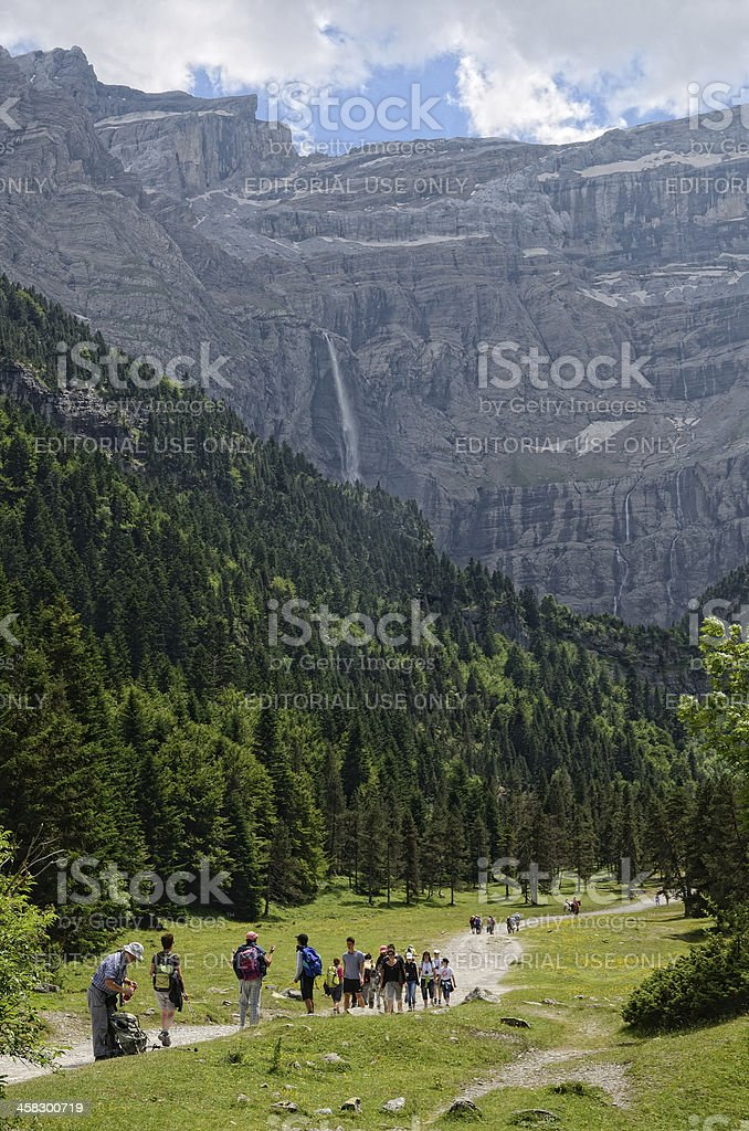 Hikers walking to the cirque of Gavarnie stock photo