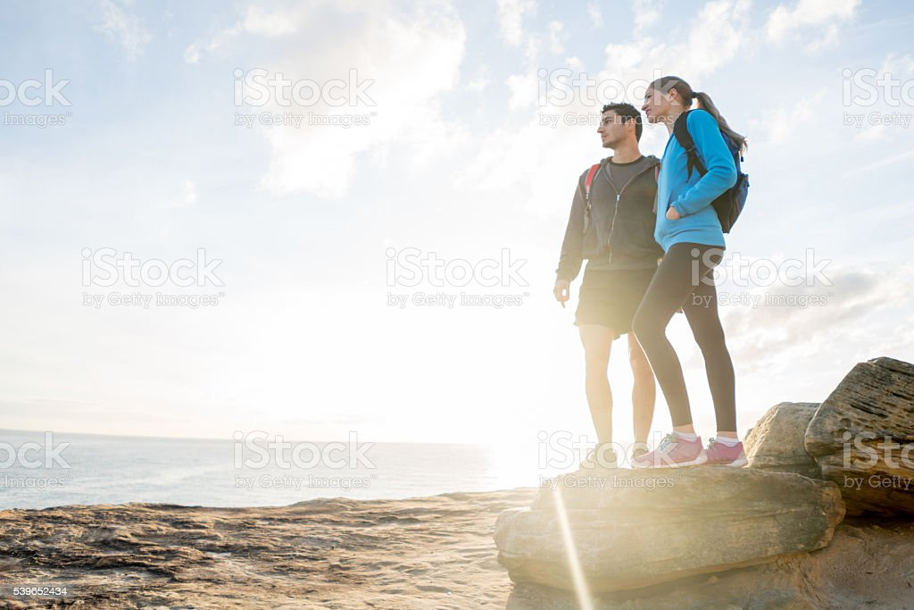Hikers watching the sunset at the beach stock photo