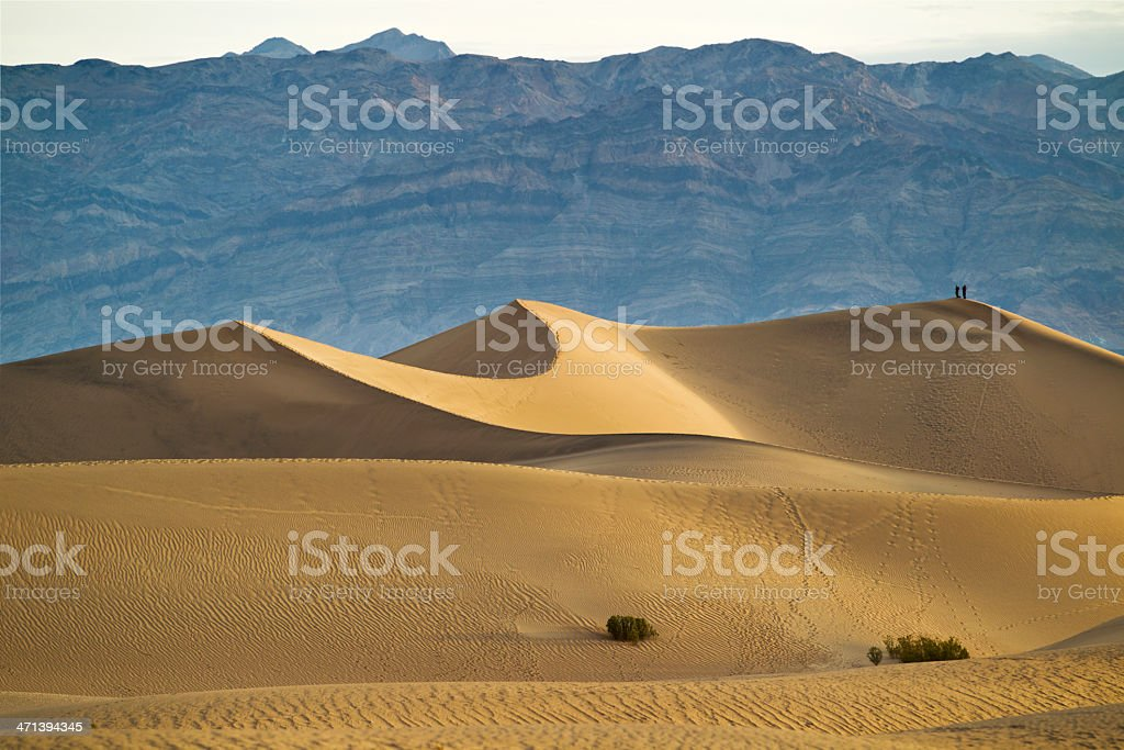 Hikers witness sunrise on Mesquite Flats Dunes in Death Valley stock photo