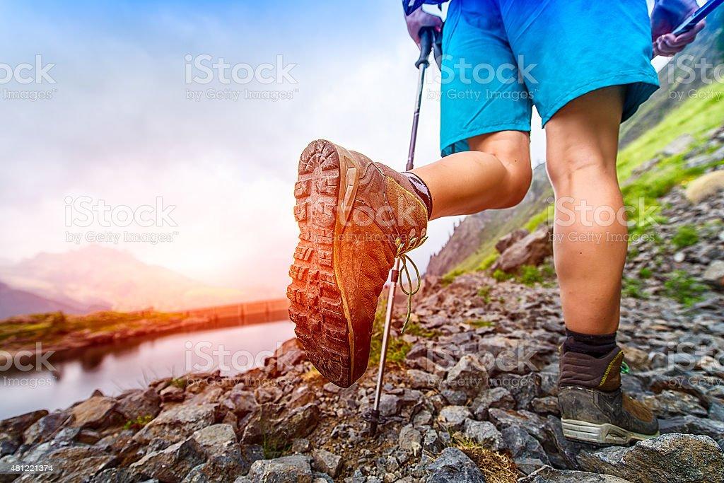 Hiking boot closeup on Mountain trail stock photo