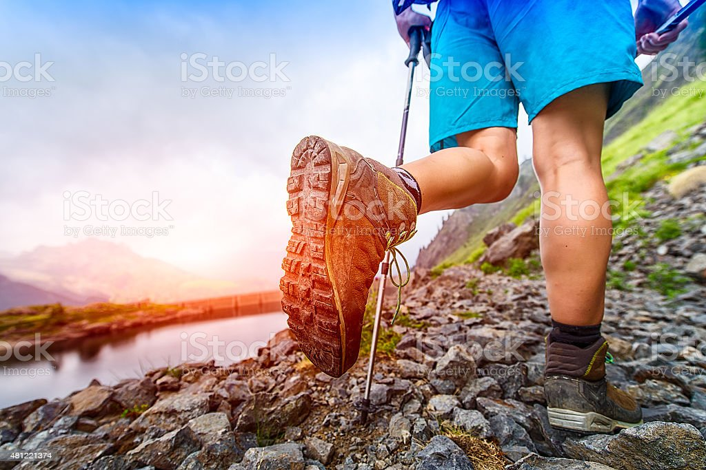 Hiking boot closeup on Mountain trail stock photo