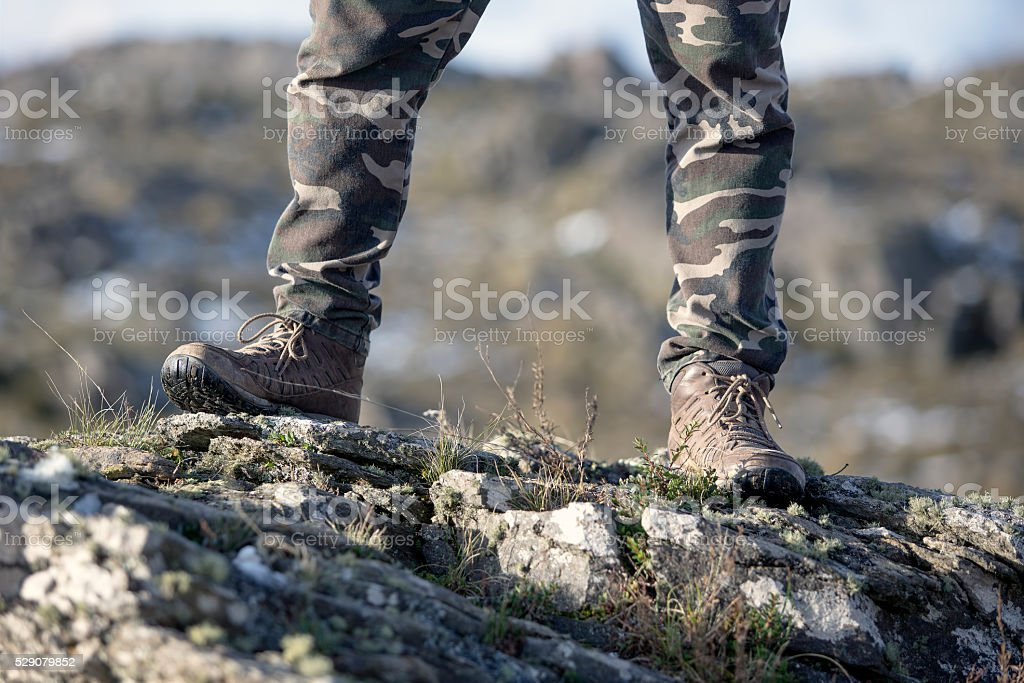 Hiking boots at mountain rocks stock photo