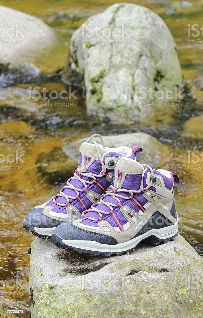 Hiking boots over a mountain stream royalty-free stock photo