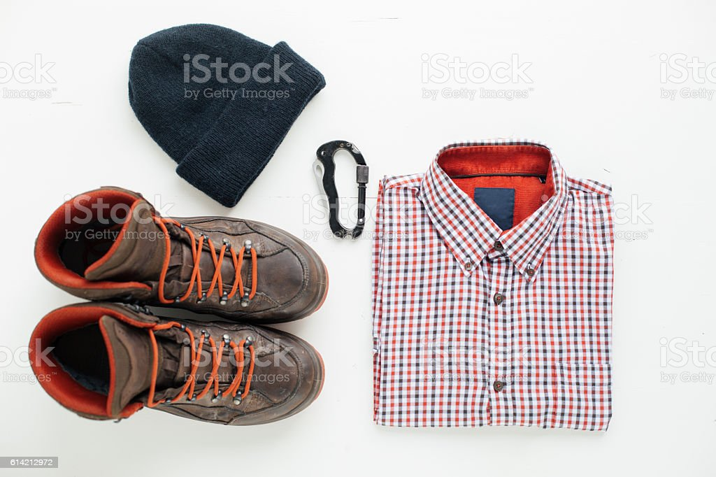 Hiking boots, plaid shirt, wool cap and carabiner stock photo