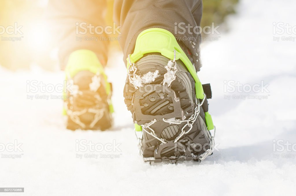 Hiking boots with equipment for ice on a snow background. stock photo