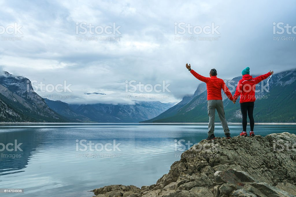 Hiking couple arms open to nature view stock photo
