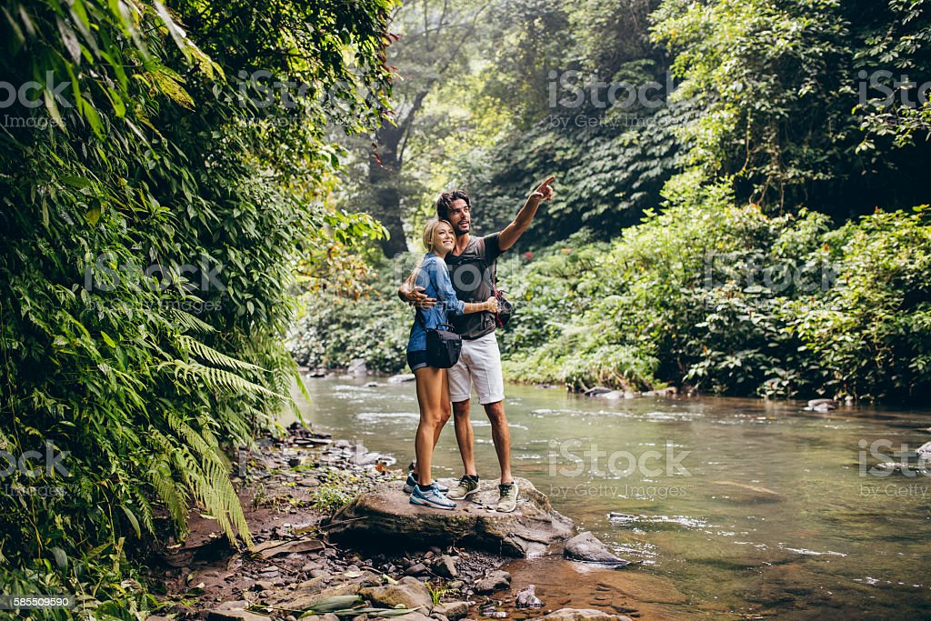 Hiking couple by stream looking at a view stock photo
