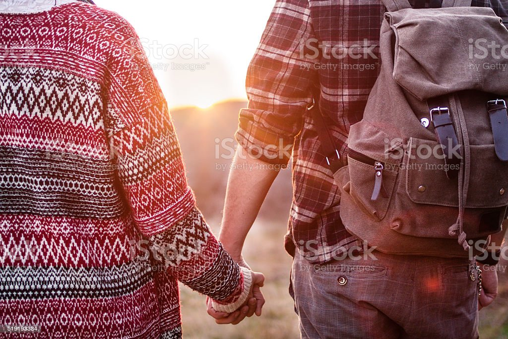 Hiking couple looking at the sunset, holding hands stock photo