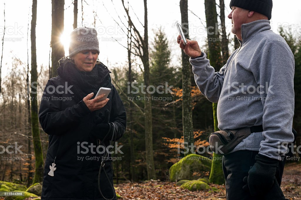 Hiking elderly couple taking a paus checking their cellphones stock photo