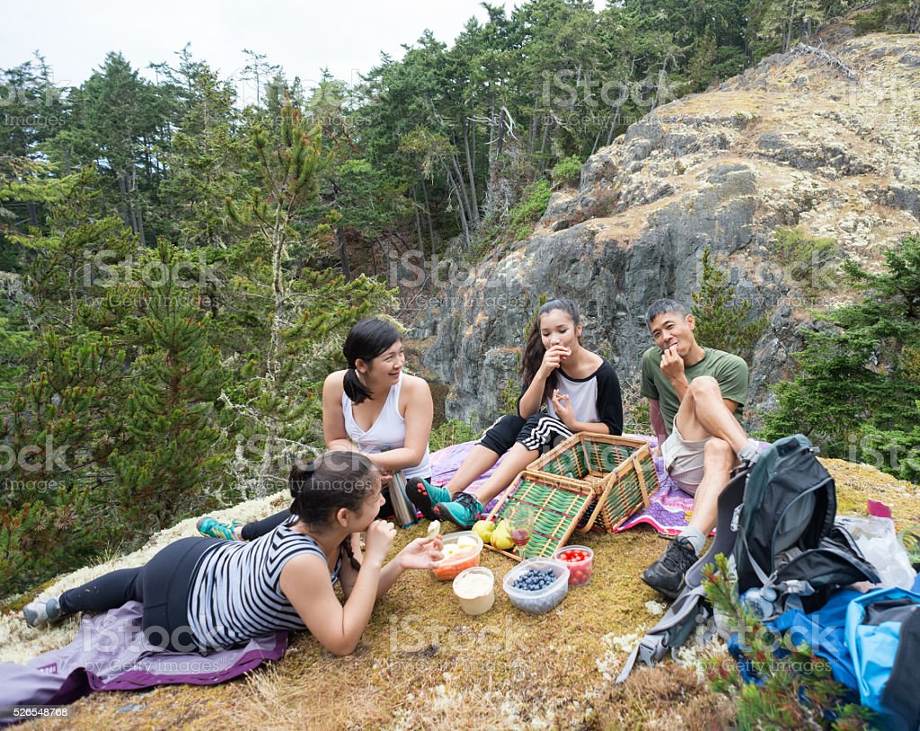 Hiking Family Eating Healthy Vegan Picnic Lunch on Wilderness Mountain stock photo