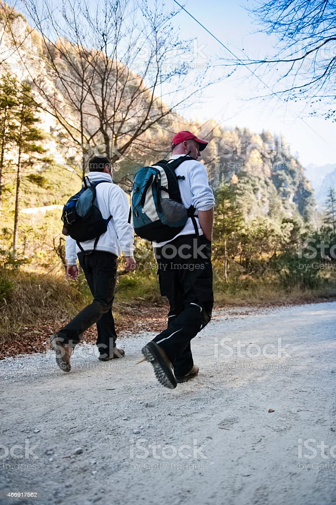 Hiking friends with backpacks walking in mountain. stock photo