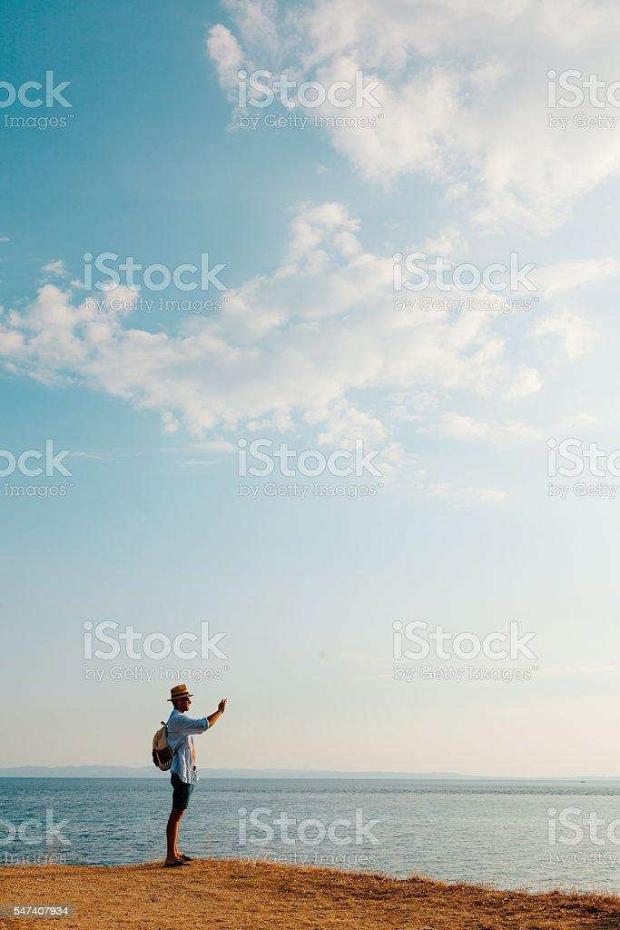 Hiking man using smart phone taking photo stock photo