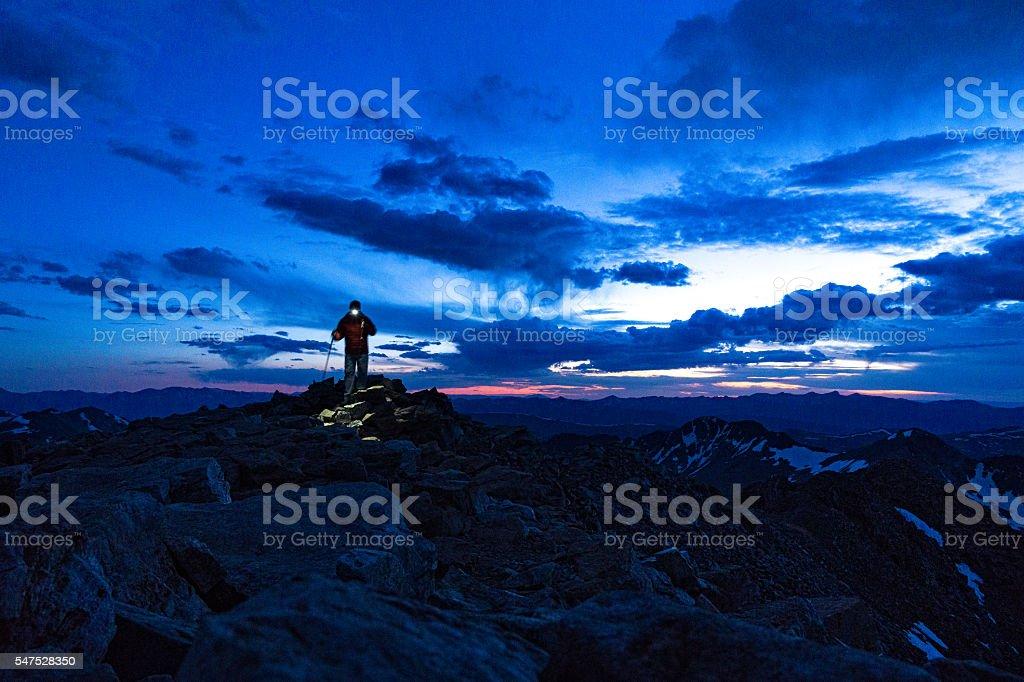 Hiking Mountain Summit at Dusk with Headlamp stock photo