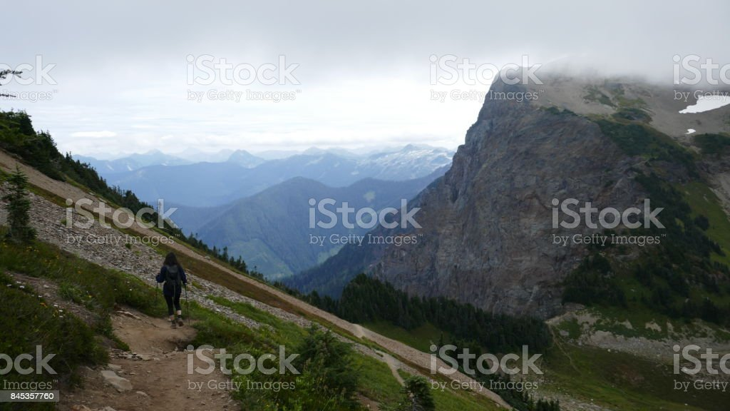 Young woman hiking through scenic mountain landscape in British...