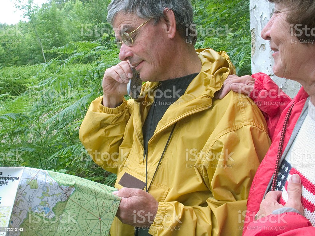 Hiking Senior man and wife on the phone with map royalty-free stock photo