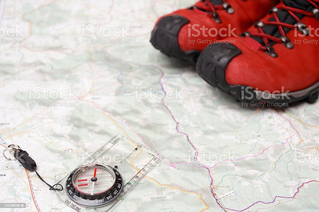 Hiking shoes and compass on a map royalty-free stock photo