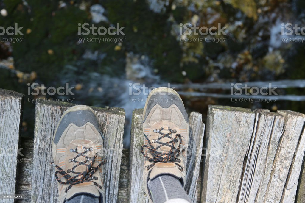 hiking shoes of a hiker on the wooden bridge stock photo