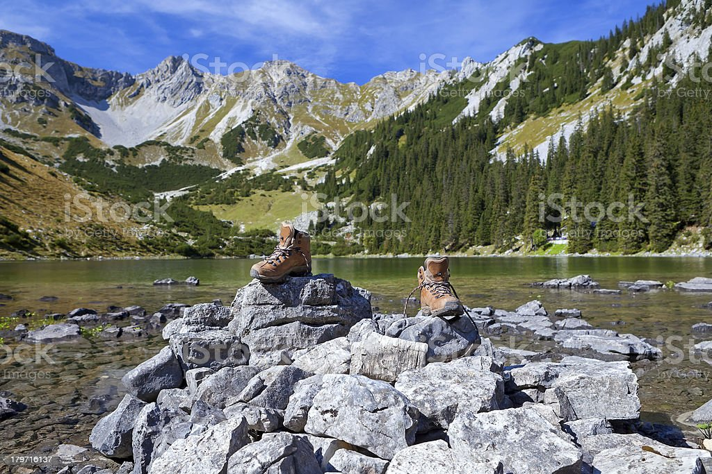 hiking shoes on rock by Alpine lake royalty-free stock photo