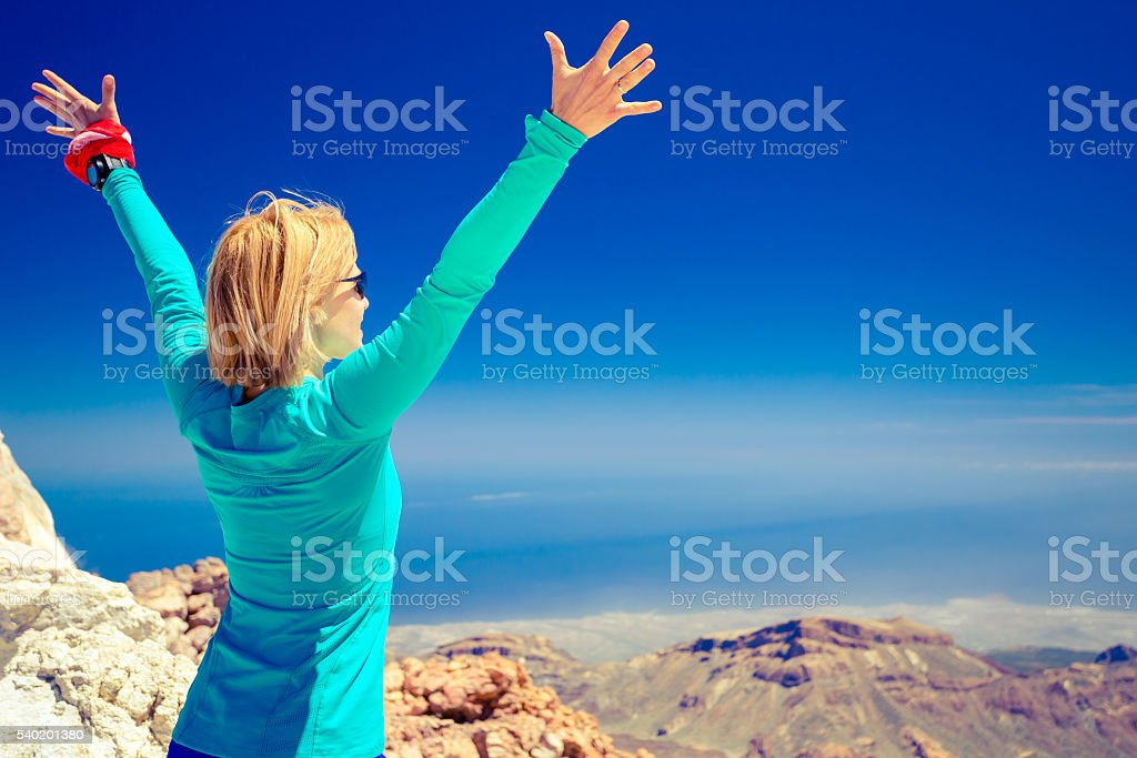 Hiking success, arms up outstretched in mountains stock photo