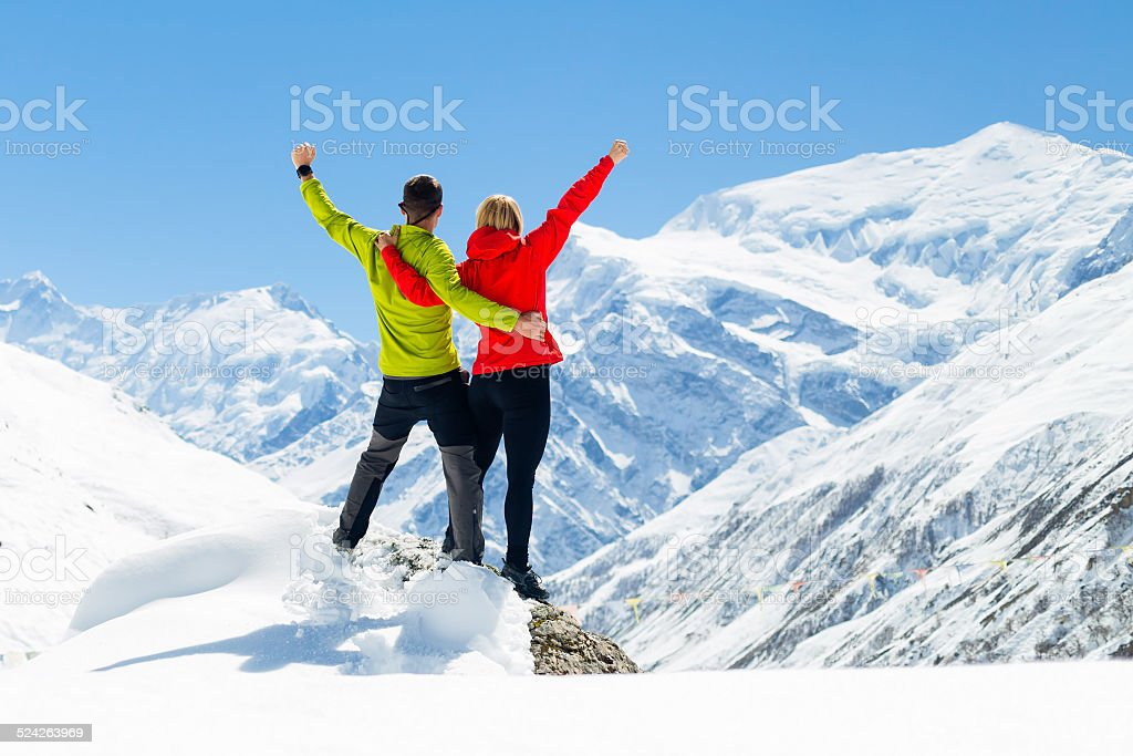 Hiking success, couple man and woman in winter mountains stock photo