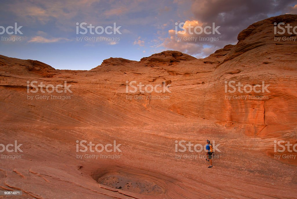 hiking: sunset sandstone landscape and small man stock photo