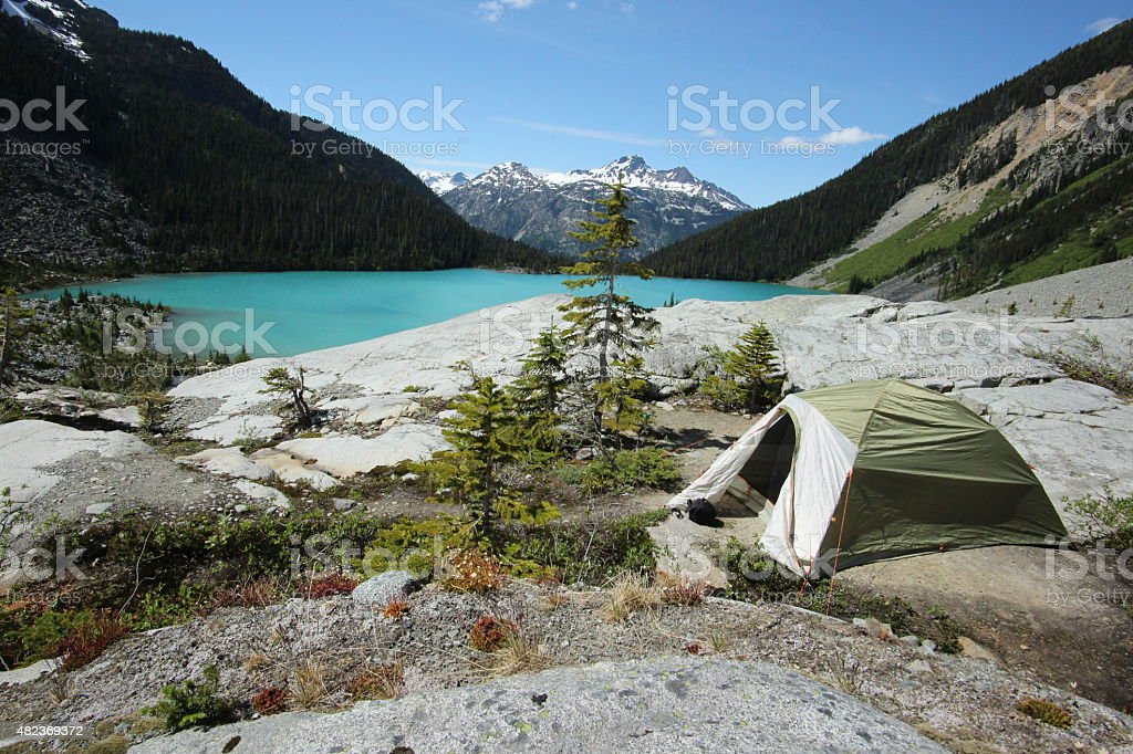 Hiking tent above a turquoise lake stock photo