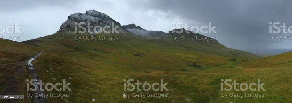 Hiking to the glacier. Tough, cold and wet weather. Wind, a lot of rain. View over mountain range. View to the glacier with ice and snow. Water drops on the lense. stock photo