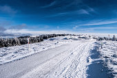 hiking trail in winter austrian mountains with blue sky