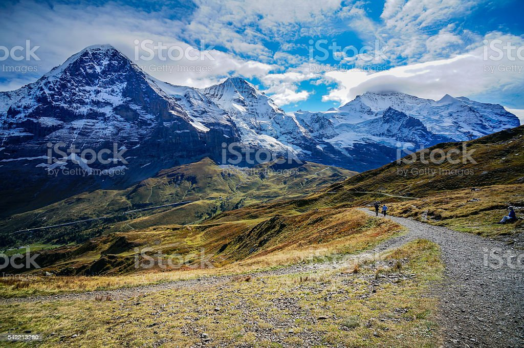 Hiking trail with the Eiger,Monch and Jungfrau summit view. stock photo