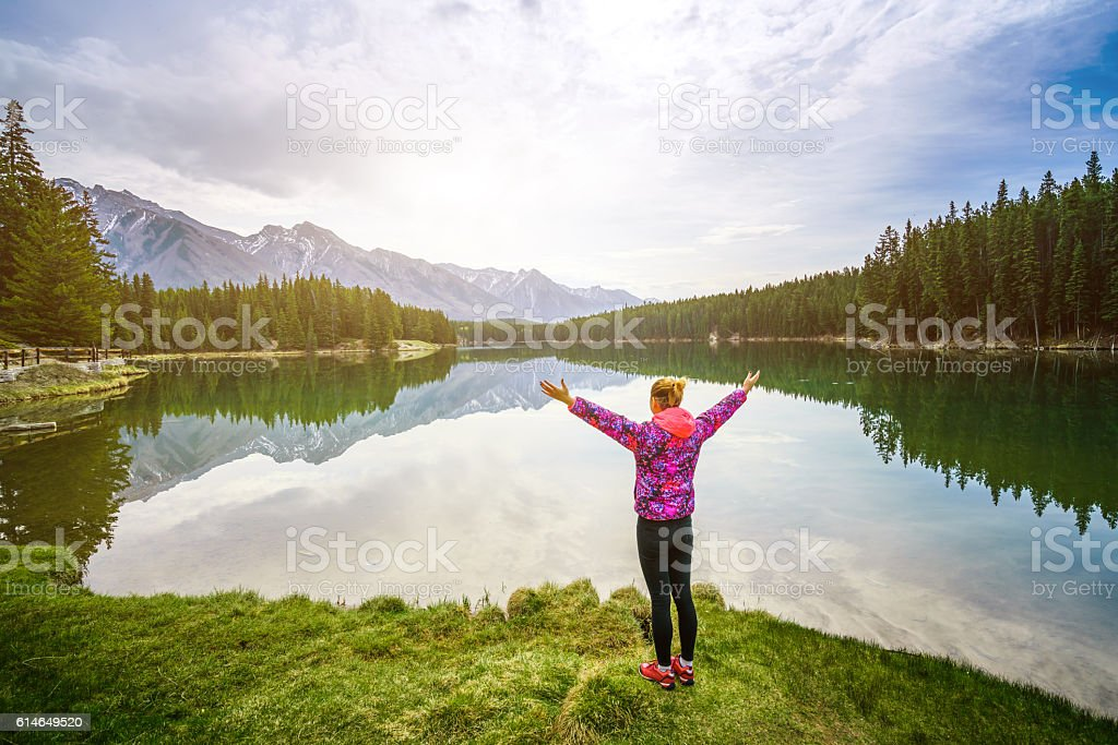 Hiking woman arms open to nature view stock photo